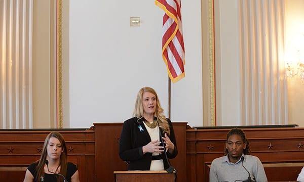 Blonde Woman Stands at a Podium Addressing the Audience with Other Board Members